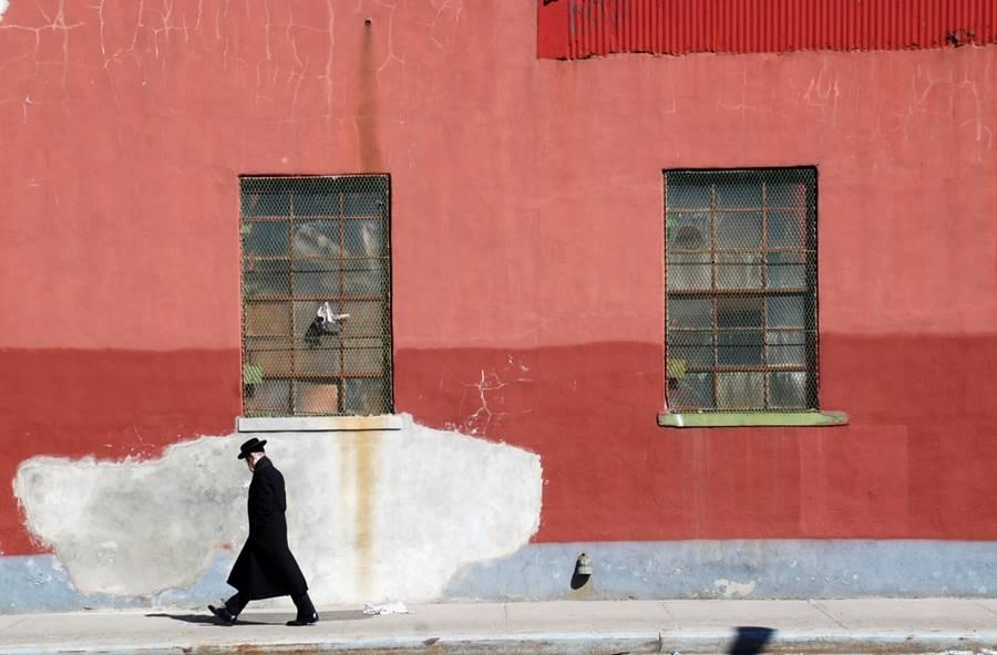 Hombre judío caminando en una calle vacía.
