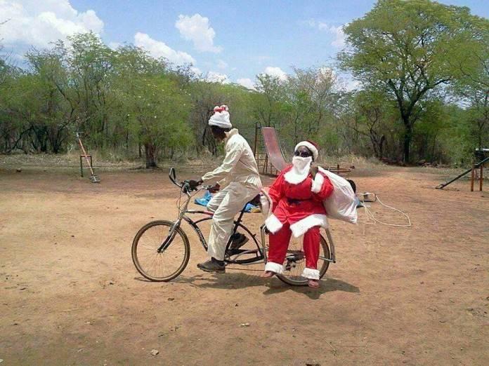 Persona negra en una selva llevando en bicicleta a un señor disfrazado de Santa Claus.