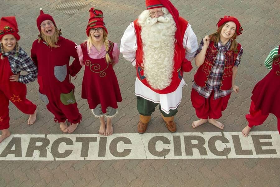 Cómo ver a Santa Claus en Finlandia - Santa en la línea del Cçírculo Polar posando con sus elfas.