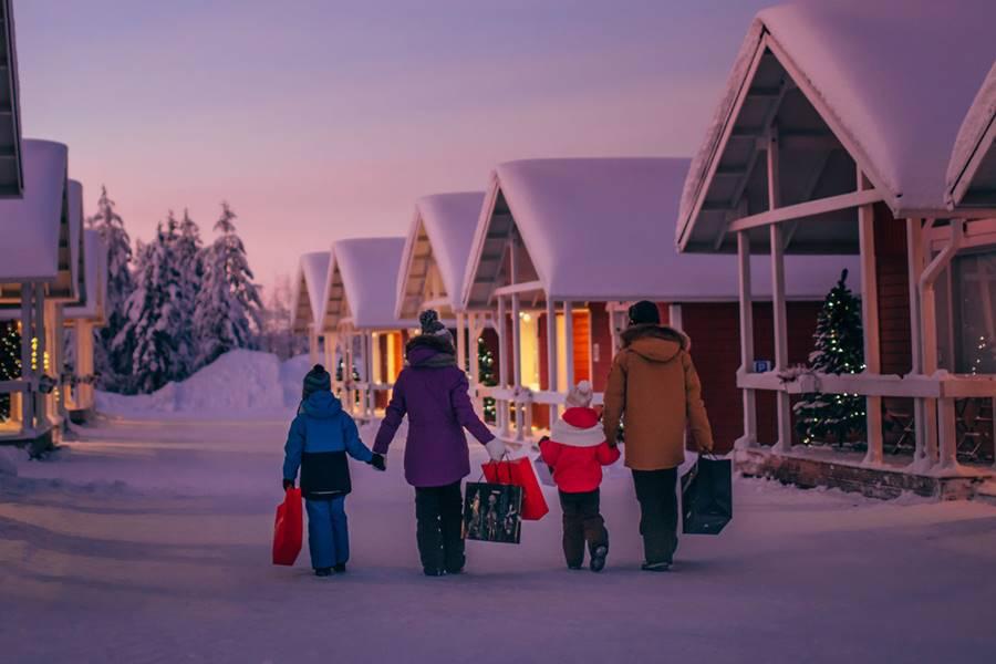 Cómo ver a Santa Claus en Finlandia - Familia caminando a su alojamiento en medio de la nieve.
