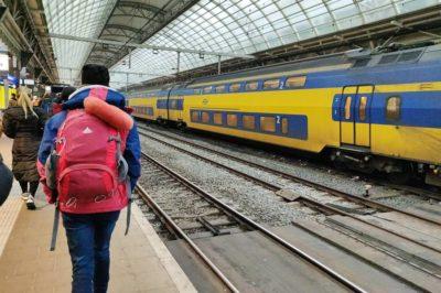 Ir del aeropuerto a Ámsterdam - Viajero en el andén de espaldas.