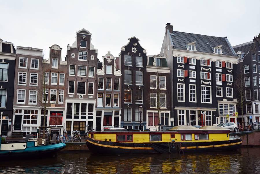 Casas de fondo frente a barcos de colores en el canal y un cielo nublado.