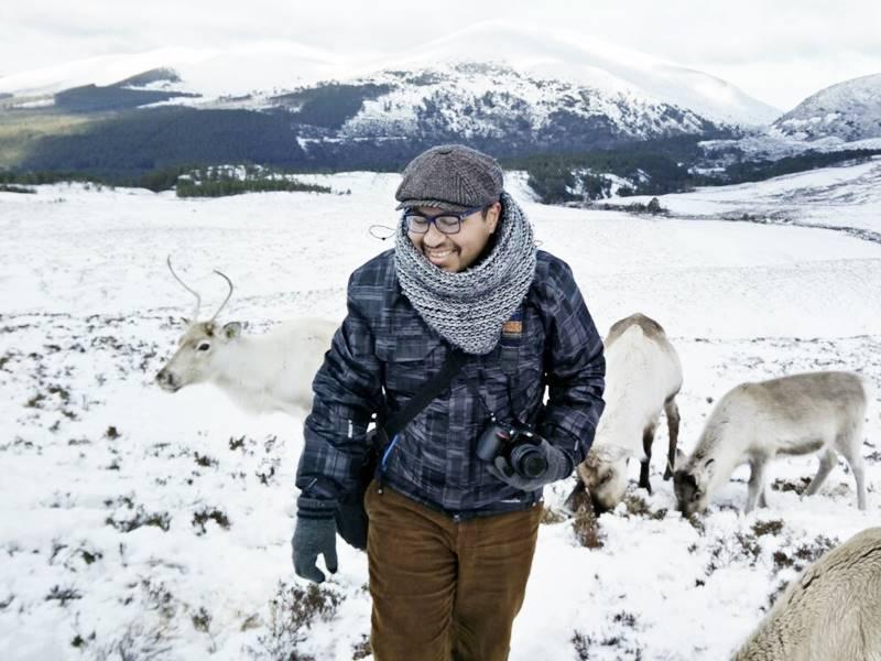 Arol con una cámara en mano en una montaña y rodeado de renos y nieve.