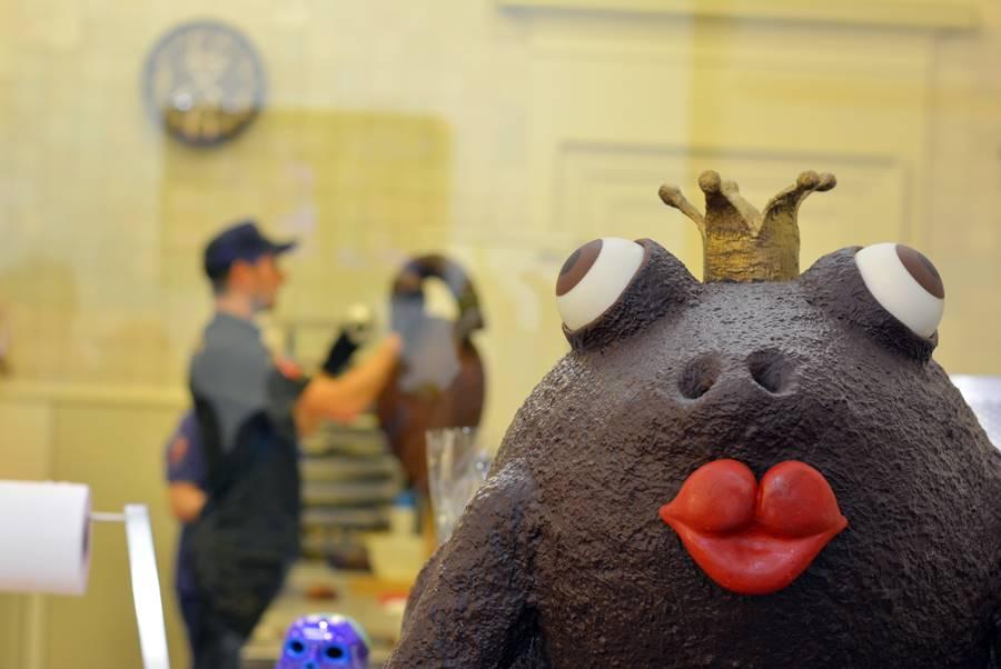 Primer plano de una rana gigante de chocolate con los labios rojos. Al fondo hay una persona creando otro muñeco de chocolate.