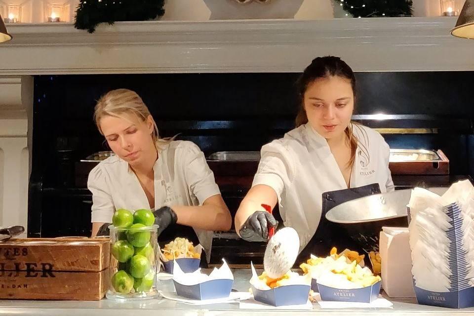 Dos chicas sirviendo patatas en Frites Atelier de Amberes.