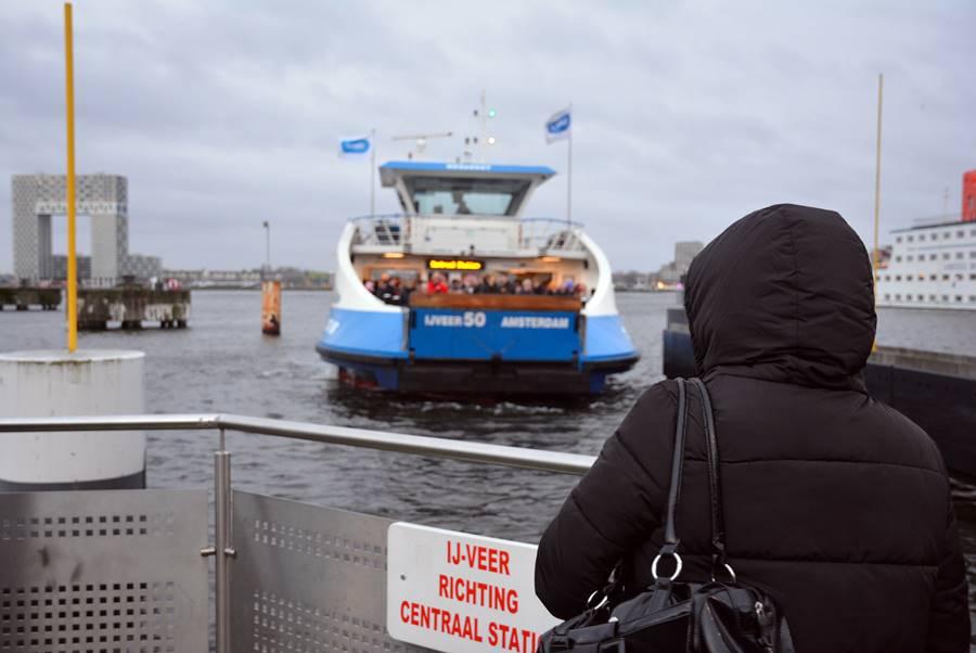 Mujer de espaldas esperando el ferry bajo la lluvia