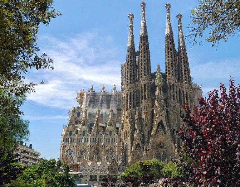 La catedral de la Sagrada Familia se ve a lo lejos detrás de unos árboles en un día soleao.