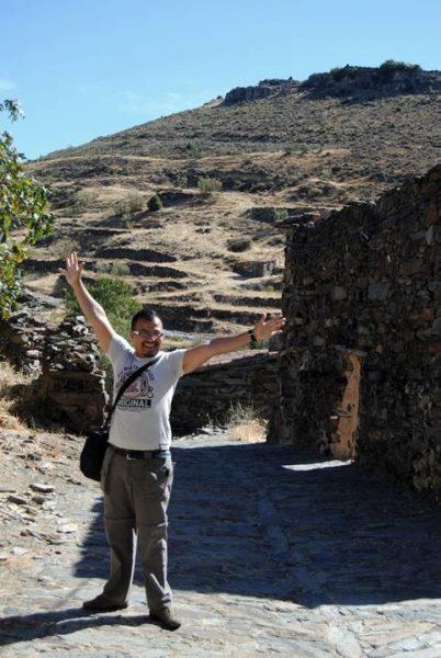 Arol levantando los brazos y mirando a la cámara en una calle pequeña de un pueblito de piedras.