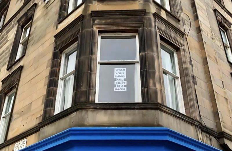 Otra ventana con un cartel que pide que no seamos racistas.