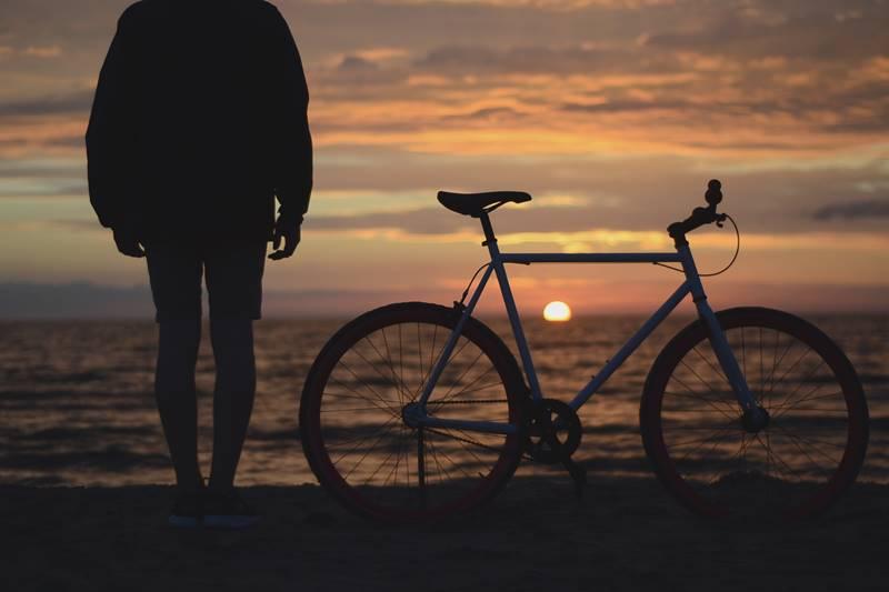 Silueta de persona frente al mar junto a su bicileta en el atardecer