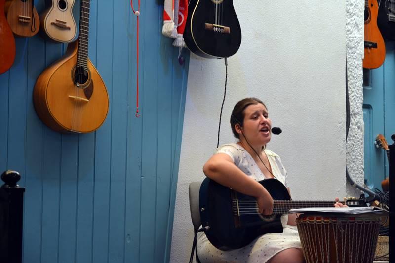 Mujer sentada con una guitarra y cantando en el restaurante.