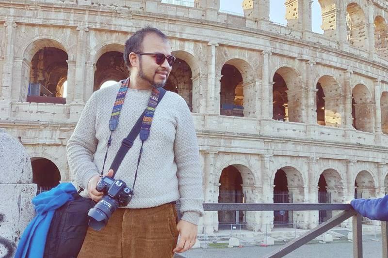 Arol sosteniendo una cámara frente al Coliseo Romano y mirando hacia la izquierda.