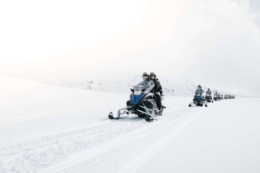 Personas en motos de nieve yendo a visitar un glaciar en Islandia.