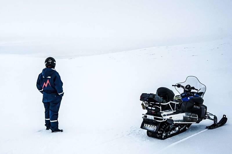 Persona posando de espaldas al visitar un glaciar en Islandia junto a una moto de nieve.