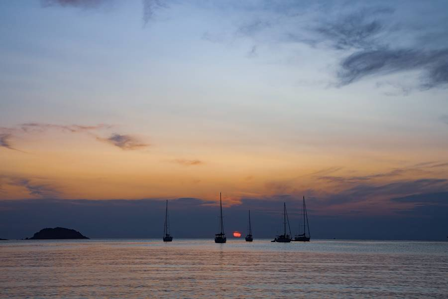 Cinco veleros en el horizonte en en el atardecer. Se ven las siluetas de los veleros.