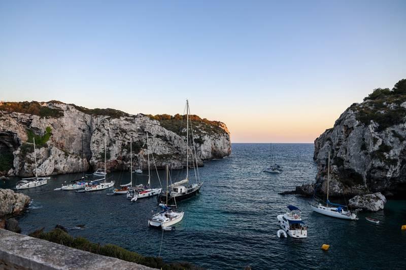 Un catamarán y dos veleros en una cala muy tranquila en Menorca.