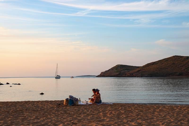 Dos personas en una playa vacía mirando el atardecer y de fondo en el mar hay un velero.