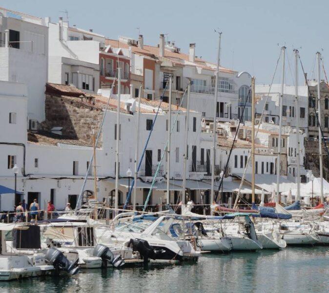 Muchas embarcaciones aparcadas frente a pisos blancos.