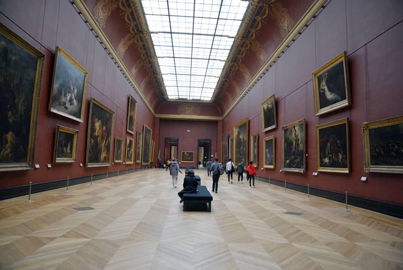 Interior del museo de Liuvre donde hay personas mirando cuadros y otras sentadas en los bancos descansando - Qué ver en París