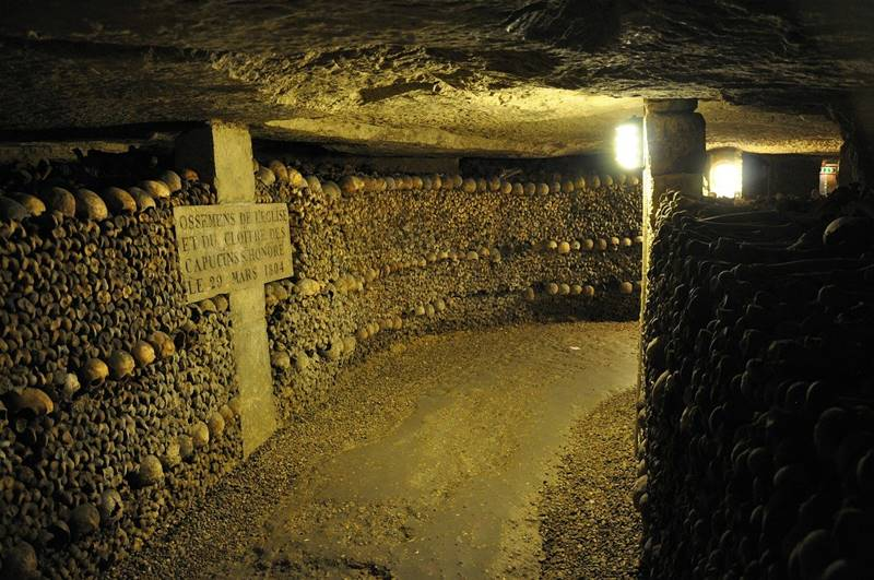Pasillo oscuro con cientos de huesos y cráneos en las paredes - Qué ver en París