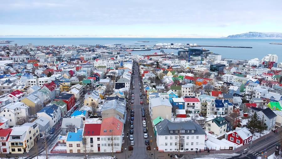 Vistas desde lo alto de la ciudad. Hay una calle larga y muchas casas con techos de colores llamativos.