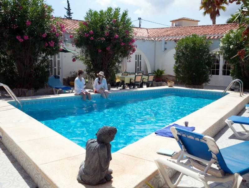 Dos mujeres hacblan al borde de una piscina cerca de una imagen de Buda - Mejores retiros Detox en España.