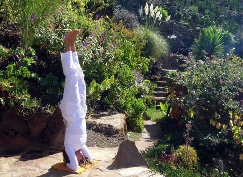 Persona haciendo una postura de yoga en un jardín - Mejores retiros Detox en España.