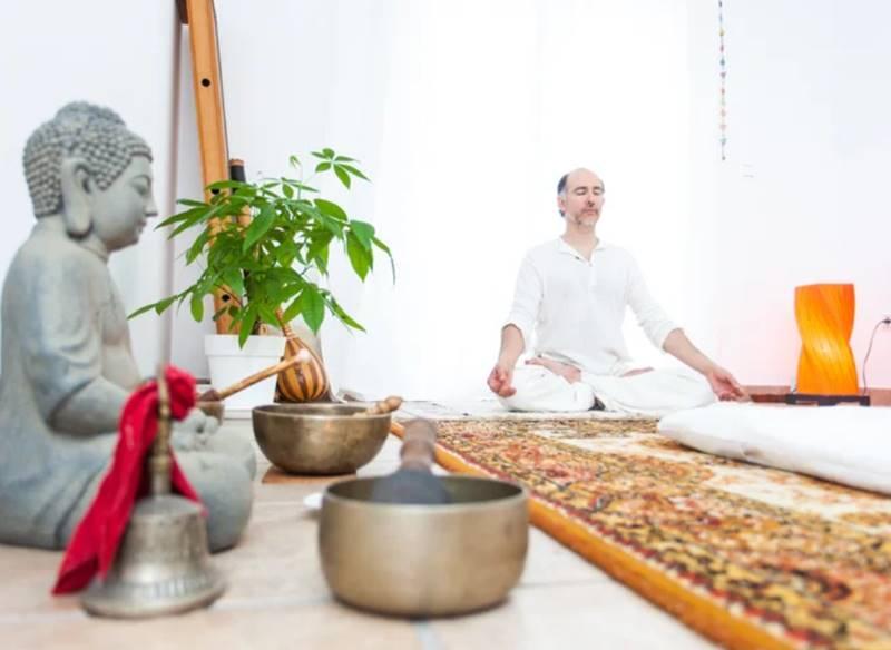 Primer plano de un cuenco tibetano y una imagen de Buda y al fondo un hombre vestido de blanco medita con las piernas cuzdas - Mejores retiros Detox en España.