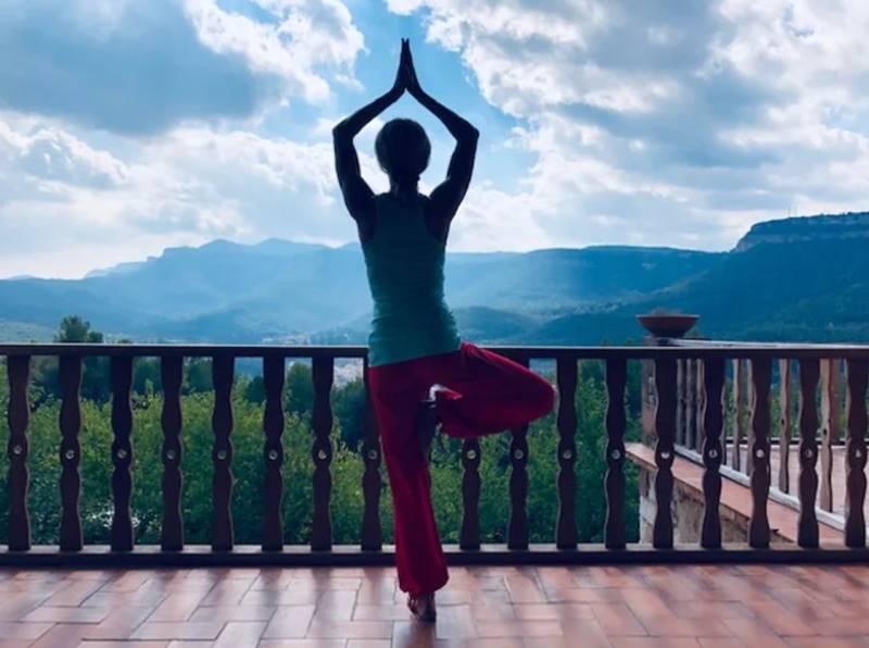 Mujer de espaldas haciendo una postura de yoga frente a las montañas - Mejores retiros Detox en España.