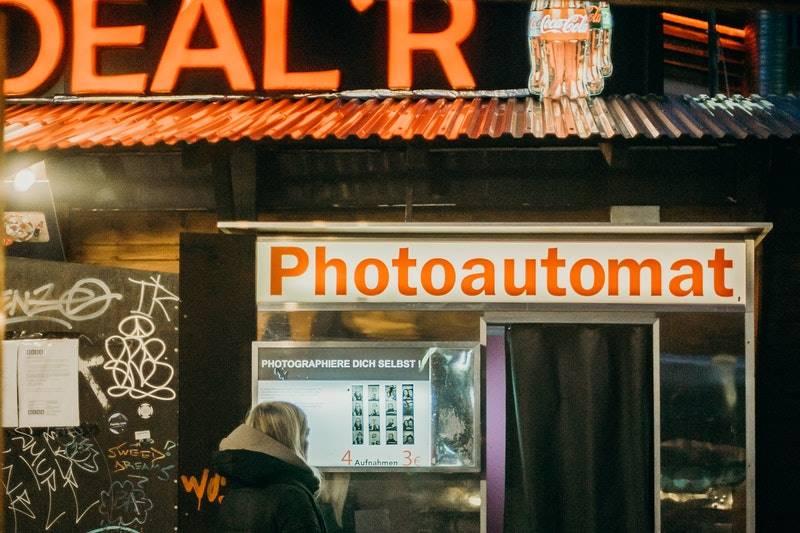 Una chica mirando un viejo fotomatón - Visitar el barrio Mitte de Berlín