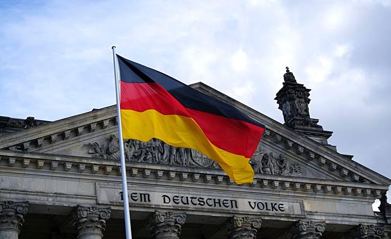 Primer plano de la bandera de alemania con el parlamento de fondo - Visitar el barrio Mitte de Berlín