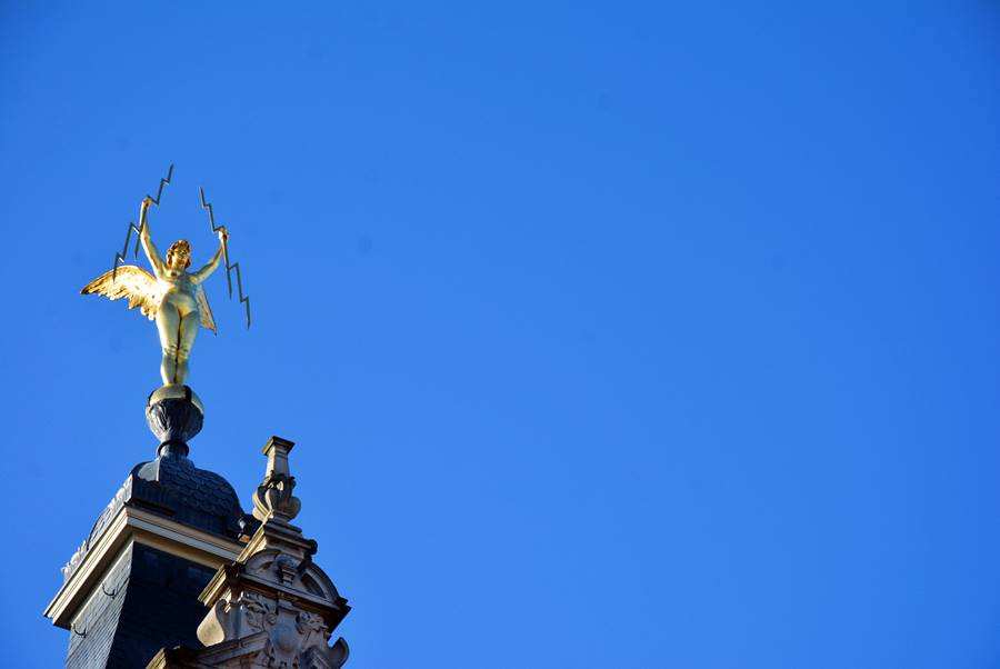Escultura dorada en Amberes con un cielo azul de fondo