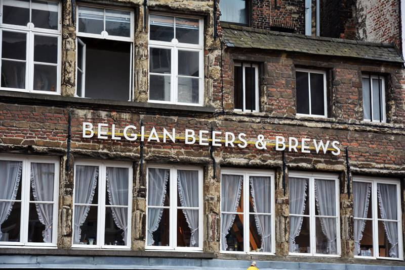 Cartel en una fachada de ladrillos que hace referencia las cervezas y los chocolates belgas