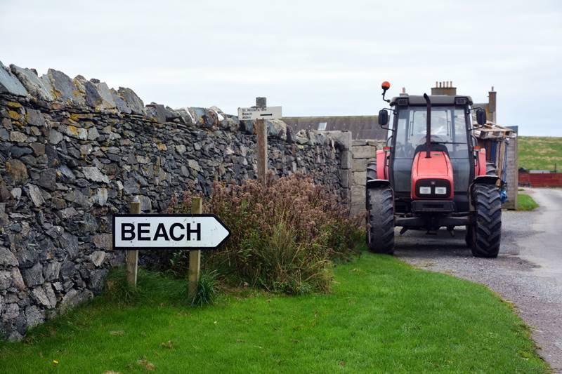 Cartel que indica la dirección a la playa con un tractor de fondo.