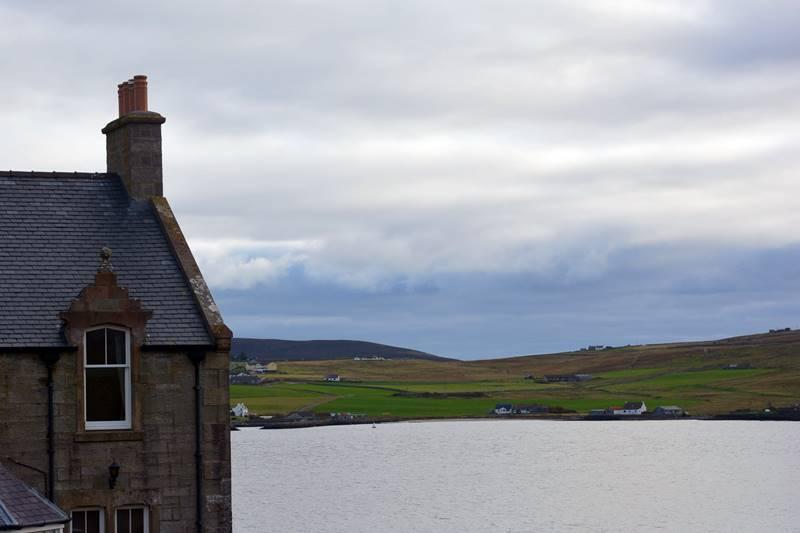 Parte de una casa y al fonde se ve la isla de Bressay.
