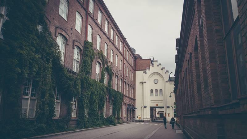 Calle vacía entre edificios de ladrillos en Helsinki.