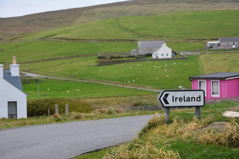 """Pequeño poblado donde se ve un cartel de carretera que dice """"Irlanda""""."""