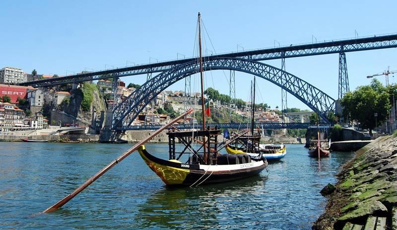 barco navegando al mediodía sobre el río bajo el puente.
