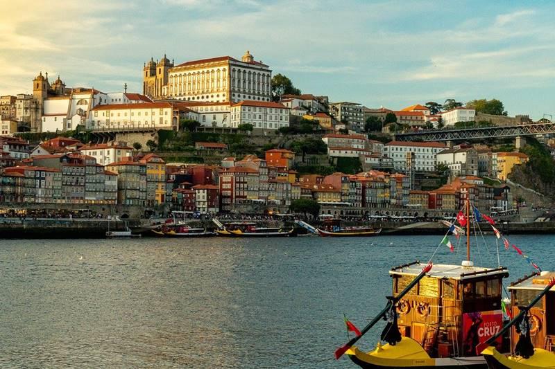 Pequeño barco con la ciudad de oporto a lo lejos