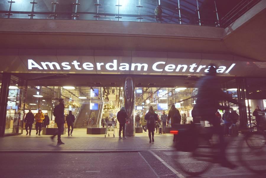 Entrada de la estación Amsterdam Central de donde sale gente y cruza una bicicleta en la noche.
