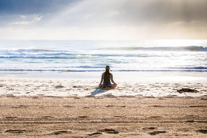 Mujer de espaldas en la playa meditando.