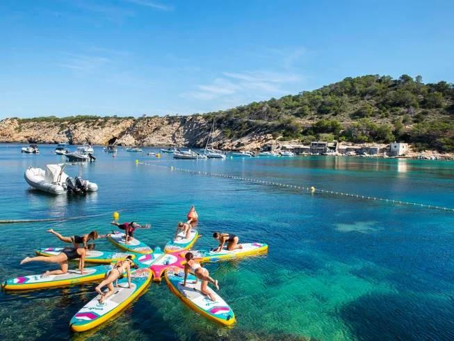 Personas haciendo yoga en el agua sobre tablas en Ibiza