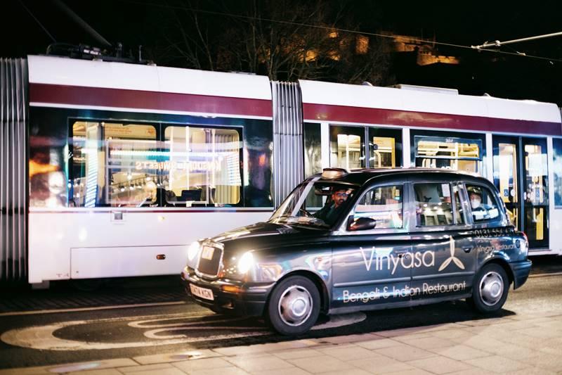 In tazi junto a un tranvía en el centro de Edimburgo