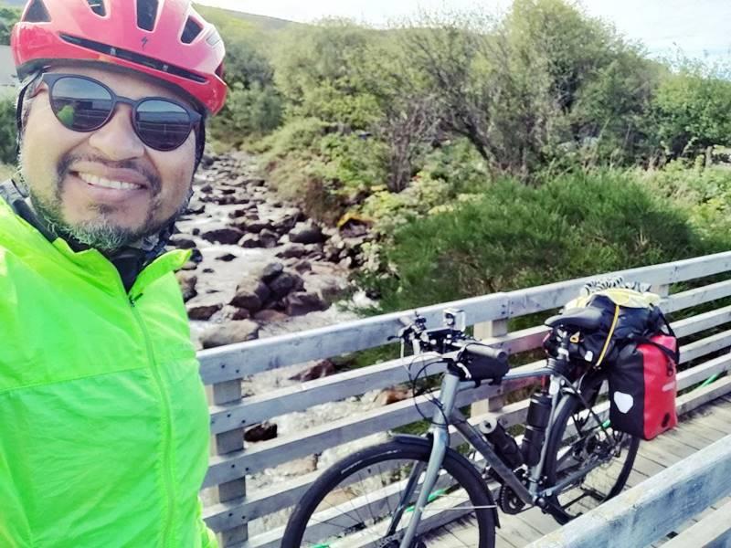 Yo con casco de bicicleta, gafas oscuras y sonrisa frente a una cascada y la bici de fondo.