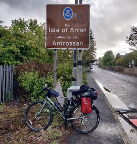 """La bicicleta apoyada en un cartel que dice """"Para isla de Arrán siga las indicaciones"""""""