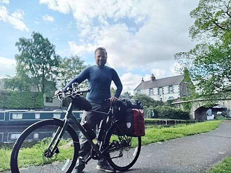 Yo junto a mi bicicleta posando con Ratho de fondo