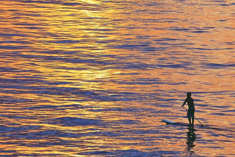 Persona haciendo paddle surf en Tenerife al atardecer.