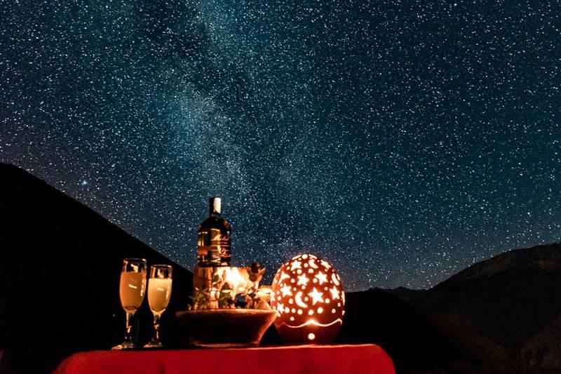 Dos copas junto a una botella bajo la vista de la Via Láctea