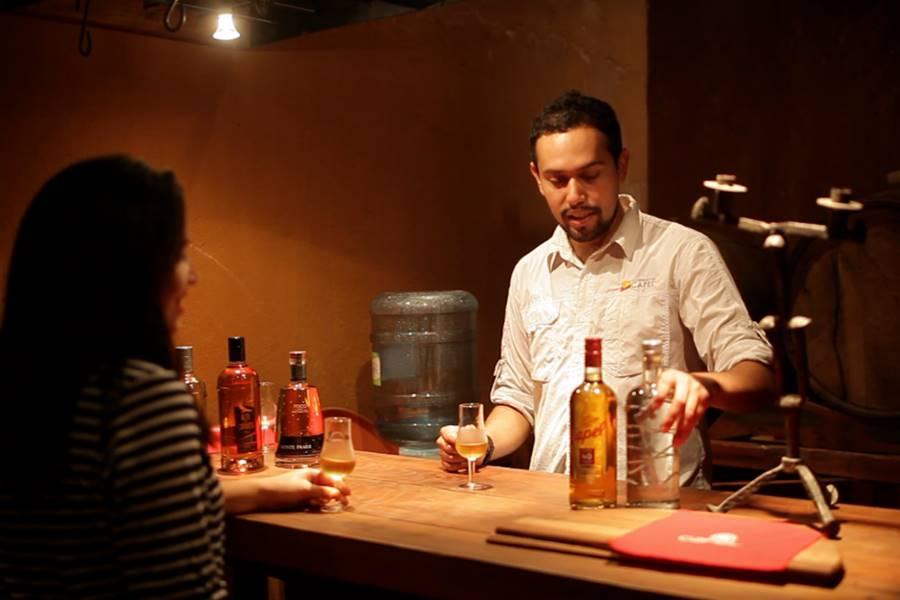 Barman preparando una cótel a base de pisco a una cliente.