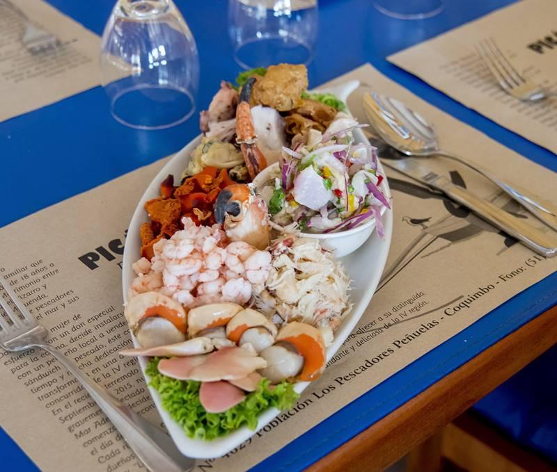 Plao de productos marinos sobre una mesa azul.